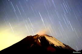 FILE - The Geminid meteor shower lights up the sky over the Mexican volcano Popocatepetl near the village of San Nicolas de los Ranchos in Puebla state, early on Dec. 14, 2004. The show for 2018 is peaking overnight on Dec. 13 and 14.