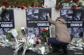 A person places flowers in front of the offices of weekly satirical newspaper Charlie Hebdo in Paris, Jan. 8, 2015.