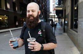 Adam Taylor, a sound engineer from Las Vegas carries two glasses of iced coffee, responds to a question about new research showing that drinking coffee may boost chances for a longer life, even for those who down at least eight cups daily, July 2, 20