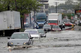 FILE - Vehicles drive on floodwaters, May 5, 2017, in Newark, N.J. Heavy rains caused flooding in New York City and flight delays in the region.