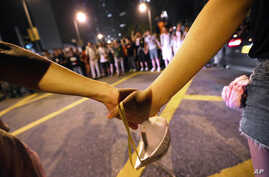 Student protesters form a human chain as part of attempts to stop other protesters from blocking a main road in front of the government complex where Chief Executive Leung Chun-ying's office is located in Hong Kong, Oct. 3, 2014.