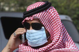 A man with mask speaks on his mobile phone in Jeddah, Saudi Arabia, May 29, 2014.