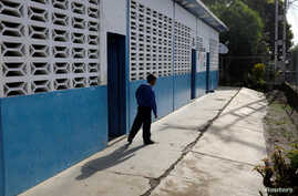 A kid walks past a classroom on the first day of school, in Caucagua, Venezuela, Sept. 17, 2018.