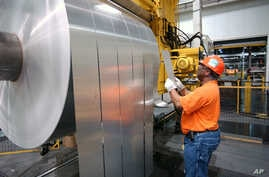 FILE - An Alcoa Warrick Operations employee inspects the finished rolls of aluminum as they come off the last stage of the production line in Indiana, April 7, 2006.