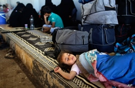 A Syrian girl who fled her home with her family due to fighting in Syria sleeps by her family's belongings at the Bab Al-Salameh border crossing in Azaz, in hopes of entering one of the refugee camps in Turkey, Aug. 23, 2012.