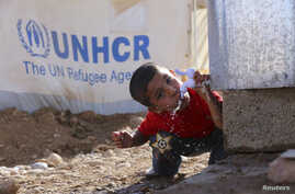 A young Syrian refugee drinks water from a tank outside a tent at a refugee camp near the city of Erbil, in Iraq's Kurdistan region, Nov. 30, 2013.