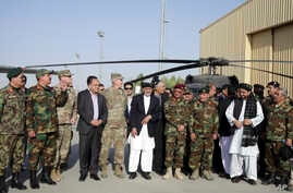 Afghanistan President Ashraf Ghani, center, poses with U.S. and local military officials during a ceremony after receiving two Black Hawk helicopters from the U.S. government, at Kandahar Air Field, Afghanistan, Oct. 7, 2017.