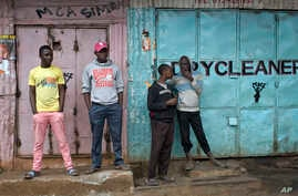 Young Kenyan men hang out in front of closed shops in Nairobi's Kibera slum Monday, Aug. 14, 2017. Kenyan opposition leader Raila Odinga urged his supporters to skip work on Monday to protest what he charged were rigged elections that gave victory to