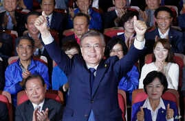 South Korea's presidential candidate Moon Jae-in of the Democratic Party raises his hands as his party leaders and members watch on television local media's results of exit polls for the presidential election in Seoul, South Korea, May 9, 2017.