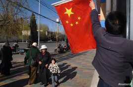 Tibetan hangs a Chinese national flag outside a residential building in Lhasa, March 28, 2009.