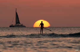 A paddle boarder looks our over the Pacific Ocean as the sun sets off of Waikiki Beach, in Honolulu, on New Years Eve, Dec. 31, 2013.