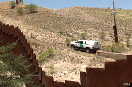 The view from the Mexican side as a US Border Patrol car passes a fence. (G. Flakus/VOA)