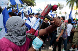 A protester poses with his homemade mortar during a protest against President Daniel Ortega's government in Managua, Nicaragua, May 30, 2018.