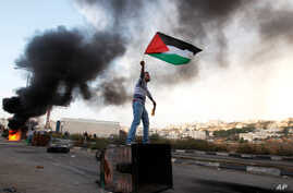 A Palestinian man waves the national flag during a protest against Israel's operations in Gaza Strip, outside Ofer, an Israeli military prison near the city of Ramallah, November 18, 2012.