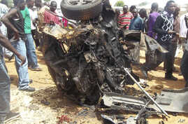 People gather around a car used by a suicide bomber following an explosion in church compound in Bauchi, Nigeria,  June 3, 2012.