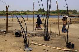 FILE - Chadian women walk past destroyed homes, in the Lake Chad shore village of  N'Gouboua, March 5, 2015.