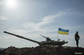 FILE - A Ukrainian soldier stands guard near a tank position close to the Russian border near Kharkiv March 24, 2014.