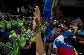A demonstrator holds up her hand with a rosary entwined, during a protest in Caracas, Venezuela, Monday, Jan. 23, 2017. Thousands of opponents of President Nicolas Maduro are marching to demand authorities set a date for overdue regional elections.