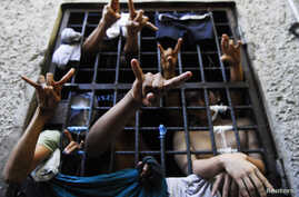 FILE - People arrested for being members of the MS-13 Mara Salvatrucha street gang among other crimes, flash their gang's hand sign from inside a jail cell at a police station in San Salvador.