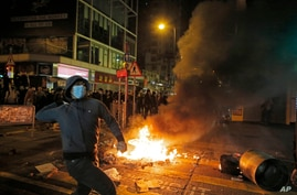 A rioter tries to throw bricks at police in Mong Kok district of Hong Kong, Feb. 9, 2016.