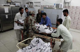 Soldiers help paramedics move the body of one of four Frontier Corps personnel killed by gunmen in Quetta, Pakistan, June 29, 2016.