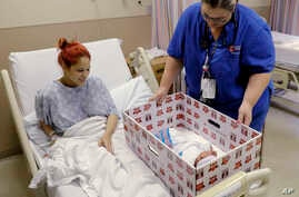 Infant Sleep Recommendations: FILE - In this May 6, 2016, file photo, Keyshla Rivera smiles at her newborn son Jesus as registered nurse Christine Weick demonstrates a baby box before her discharge from Temple University Hospital in Philadelphia on F