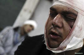 FILE - Protesters wounded during clashes with Egyptian riot police near Tahrir Square in Cairo.