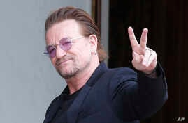 FILE - U2 singer Bono makes a peace sign as he arrives for a meeting at the Elysee Palace, in Paris, France, July 24, 2017.