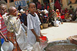 Internally displaced Somali children line up with containers in hand to receive food aid at a food distribution center in Mogadishu (File)