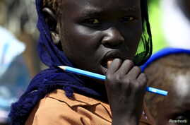 FILE - A girl waits to receive food provided by the United Nations' World Food Programme at a camp for internally displaced persons in Azaza, east of Ad Damazin, capital of Blue Nile state in Sudan, Oct. 21, 2015.