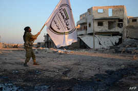 A Turkish-backed Syrian rebel holds the flag of his division in the northwestern border town of al-Bab on Feb. 23, 2017, after they fully captured the town from the Islamic State (IS) group.