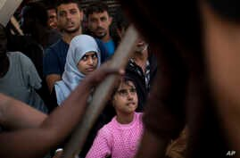 Migrants and refugees wait to leave the Golfo Azzurro rescue vessel as they arrive at the port of Pozzallo, south of Sicily, Italy, with hundreds of migrants aboard, rescued by members of Proactive Open Arms NGO, June 17, 2017.