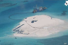 In this photo taken by surveillance planes and released May 15, 2014 by the Philippine Department of Foreign Affairs, a Chinese vessel, top center, is used to expand structures and land on the Johnson Reef, called Mabini by the Philippines and Chigua