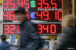 FILE - People pass by a board displaying exchange currency rates in Moscow, April 3, 2014.