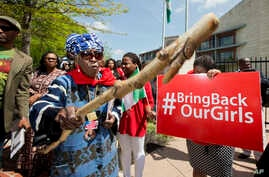 A protester brandishes a wooden stick during a rally in front of the Nigerian embassy in northwest Washington, May 6, 2014, protesting the kidnapping of nearly 300 teenage schoolgirls from a school in the remote northeast of Nigeria three weeks ago.