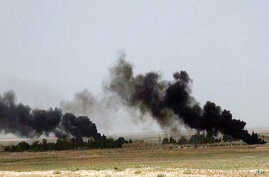 This picture released on Wednesday, May 20, 2015 on the website of Islamic State militants, shows black columns of smoke rising through the air during a battle between Islamic State militants and the Syrian government forces on a road between Homs an