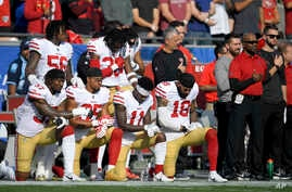 FILE - Members of the San Francisco 49ers kneel during the national anthem before an NFL football game against the Los Angeles Rams, Dec. 31, 2017, in Los Angeles.