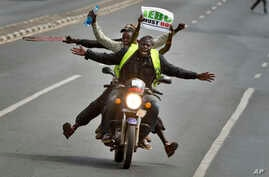 A motorcycle carrying protesters holding a placard using the acronym of the national electoral commission, drives ahead of demonstrators on foot calling for the disbandment of the commission over allegations of bias and corruption, in downtown Nairob