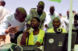 FILE - Officials from the Independent Electoral and Boundaries Commission (IEBC) assist residents to confirm their data during the launch of the 2017 general elections voter registration exercise within Kibera slums in Kenya's capital Nairobi, Januar