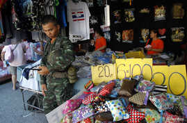 Thailand's junta kept many of the thousands of troops and police off the streets as the number of people making a public show of dissent to the May 22 coup dwindled. A soldier stand guards at a shop at Chatuchak market in Bangkok, Thailand, June 8, 2