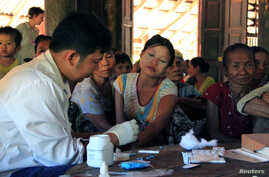 A government health worker takes a blood sample from a woman to be tested for malaria in Ta Gay Laung village hall in Hpa-An district in Kayin state, southeastern Myanmar, Nov. 28, 2014.