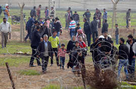 Syrians cross the border from the Syrian town of Ras al-Ain to the Turkish border town of Ceylanpinar after an air strike by Syrian government forces, December 3, 2012.