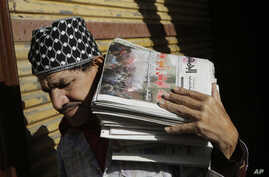 An Egyptian carries a load of newspapers fronted by pictures of clashes following the verdict in the trial of ousted President Hosni Mubarak in Cairo, Egypt, Dec. 1, 2014.