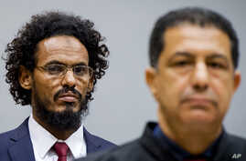 Ahmad Al Mahdi Al Faqi, left, enters the court room for his initial appearance at the International Criminal Court in The Hague, Netherlands, Sept. 30, 2015.