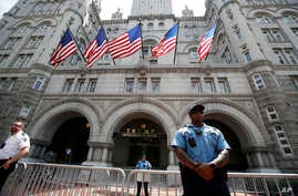 FILE - Law enforcement officers stand guard in front of the Trump Hotel in Washington, June 30, 2018.