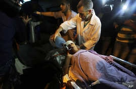Palestinian medics transport a wounded boy after an Israeli air strike targeted a motorcycle to Kamal Adwan hospital, in the northern Gaza Strip town of Beit Lahiya, northern Gaza Strip, June 11, 2014.