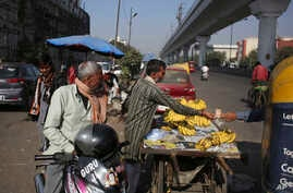 FILE -  Jitendra Prasad takes money for bananas sold to an autorickshaw driver near Azadpur Mandi, Asia's largest wholesale market for fruits and vegetables in New Delhi, India, Nov. 22, 2016.