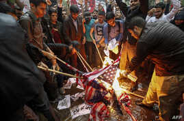 Iranians pour fuel on US flags set aflame during an anti-US demonstration outside the former US embassy headquarters in the capital Tehran on May 9, 2018.