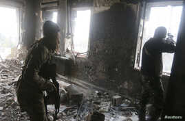 Rebel fighters take positions inside a damaged building during clashes with forces loyal to Syria's President Bashar al-Assad in Aleppo's historic citadel Dec. 7, 2014.
