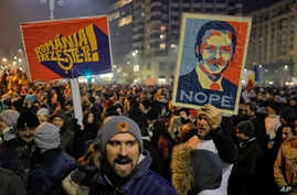 """People hold posters depicting the leader of the ruling Social Democratic party, Liviu Dragnea, the other reading """"Romania-Wake Up"""" during a protest in Bucharest, Romania, Feb. 1, 2017."""